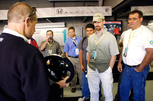 Steve Wolf demonstrates the new paddle shifting features on the IndyCar steering wheel to EPIC members at the Team Ethanol garage the day before the 2008 Indy 500