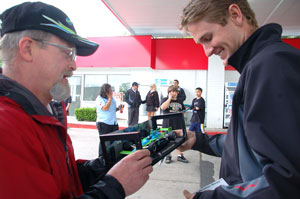 Ryan Hunter-Reay autographs a replica of the Team Ethanol No. 7 IndyCar for a race fan